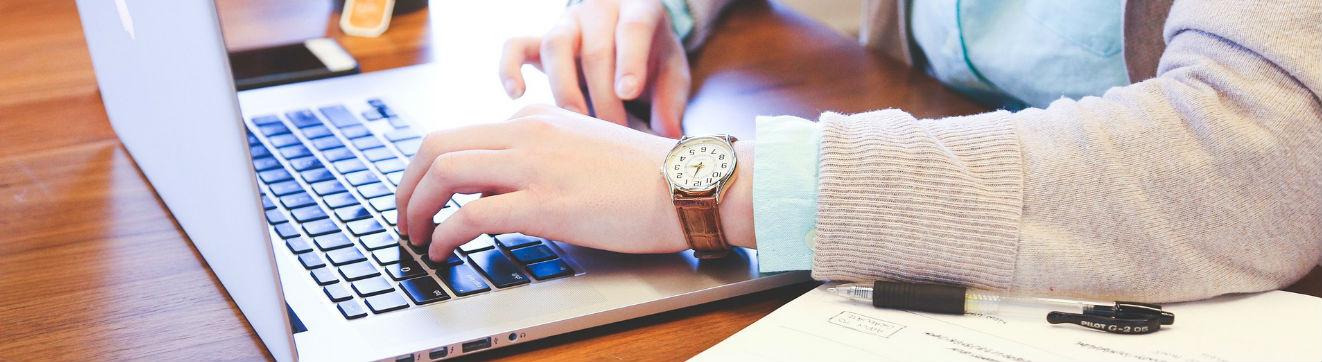 Femme écrivant sur son ordinateur portable